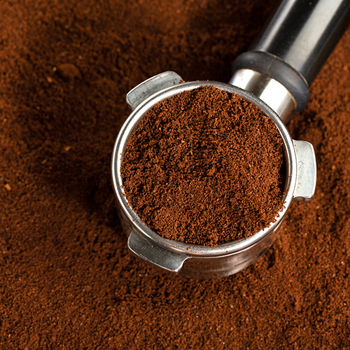 Coffee background. Coffee automatic from machine with ground coffee  on coffee background. Closeup.
